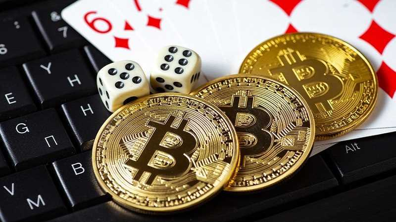Bitcoins on a laptop keyboard with cards and dice