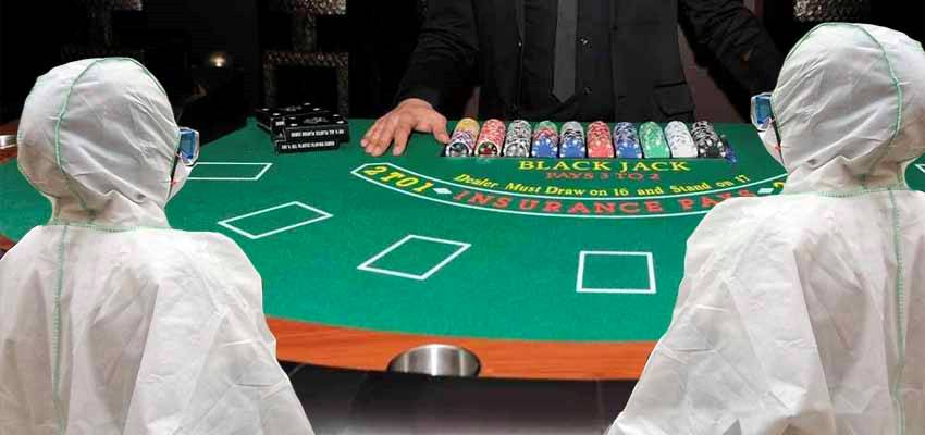 two people in hazmat suits playing at a blackjack table