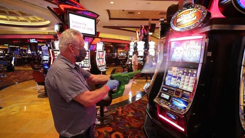 a casino worker sanitizing a gaming machine in an atlantic city casino