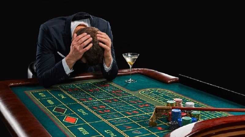 man with his head in his hands losing at a casino game