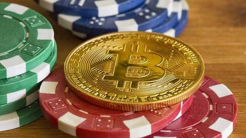a gold bitcoin token on top of poker chips