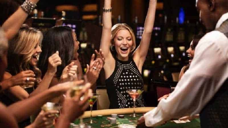 woman with arms raised winning at a casino table game